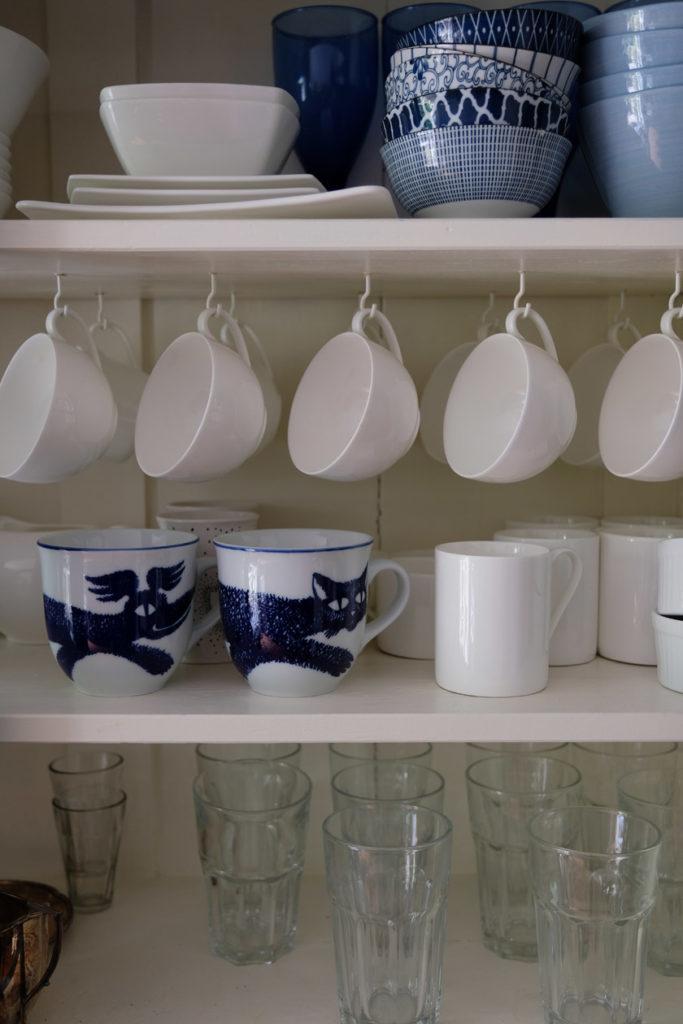 Tassen werden an kleinen Haken in den Küchenschrank gehängt