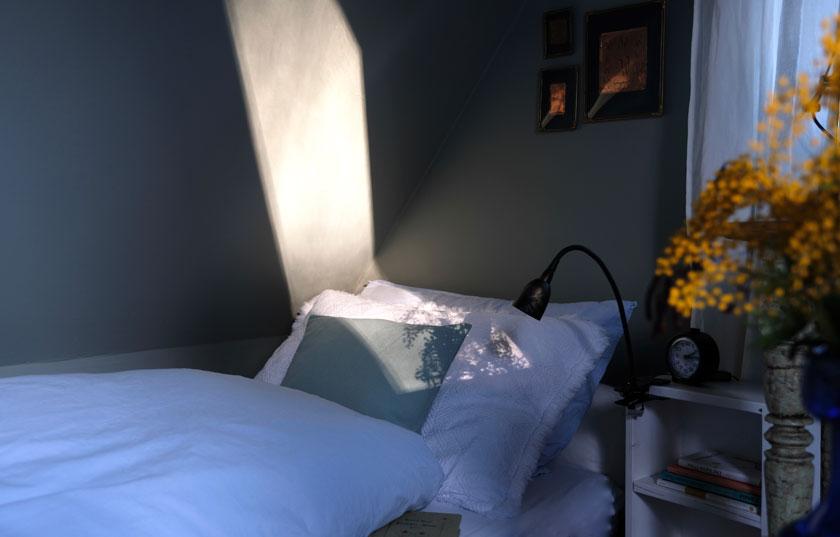 Ein stilles Graugrün verleiht einem Mini-Zimmer unterm Dach ein tolles Flair. Weiß, kleine Farbakzente und Vintage-Fundstücke sorgen für Atmosphäre.