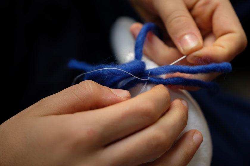 Das Stofftier bekommt Haare aus Wolle