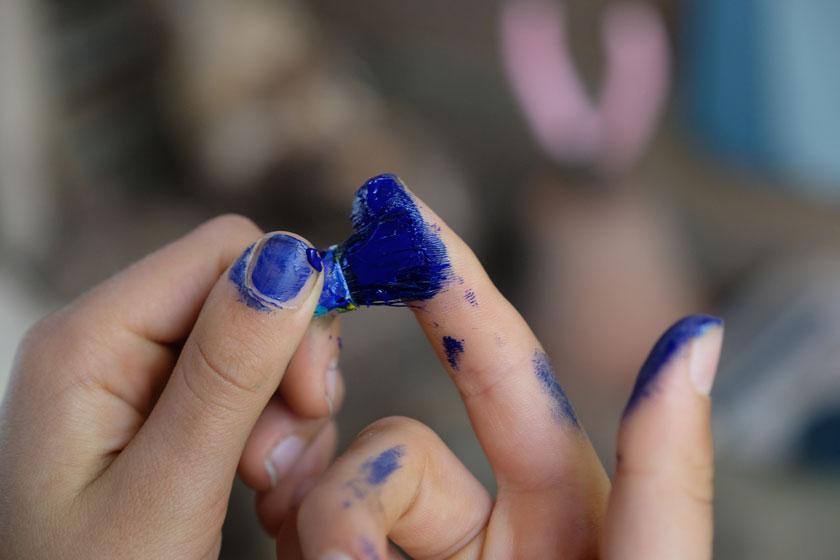 Die Borsten eines Pinsels werden Blau gefärbt und dienen als Federschopf