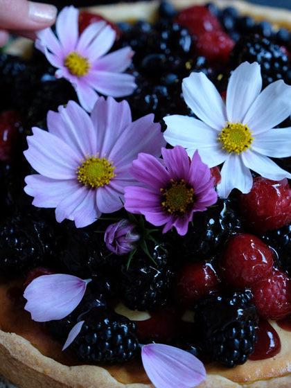 Käsekuchen mit Beeren und Blüten